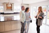 Female Realtor Showing Couple Interested In Buying Around House poster