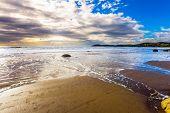 The Pacific ocean tide begins. New Zealand. Moerakis huge round boulders on a sandy beach. The sun poster