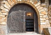 Semicircular wooden door with metal finishing in a stone wall.