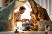 family, hygge and people concept - happy father and little daughter playing tea party in kids tent a poster
