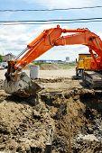 Orange Mechanical Digger And Hole