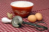 Vintage hand egg beater, bowl and eggs.