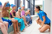Female Coach Giving Children In Swimming Class Briefing As They Sit On Edge Of Indoor Pool poster