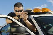 image of pistol  - Police officer aiming with pistol by car - JPG