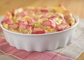 Rhubarb pie in a baking dish on a rustic table