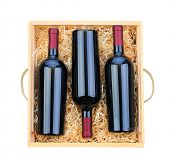 Closeup of three red wine bottles in a wooden case with packing straw. Overhead shot on a white back