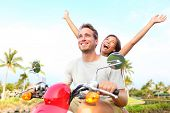 Happy free freedom couple driving scooter excited on summer holidays vacation. Young multiethnic cou