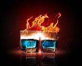 Image of two glasses of burning emerald absinthe