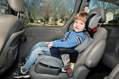 stock photo of seatbelt  - Boy in a booster seat in the back of a van - JPG