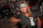 picture of frown  - Frowning female motorcycle gang member sitting in bar - JPG