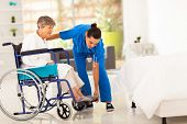 stock photo of scrubs  - young caregiver helping elderly woman on wheelchair - JPG