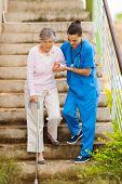 caring nurse helping senior patient walking down stairs
