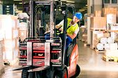 stock photo of forklift  - forklift driver in protective vest driving forklift at warehouse of freight forwarding company - JPG