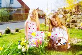 Children on an Easter Egg hunt on a meadow in spring, a living Easter Bunny is sitting in the Easter