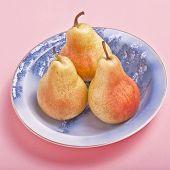 Three bartlett pears in a blue bone china dish.