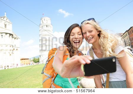 Travel tourists friends laughing taking photo with smartphone. Women girlfriends traveling in Europe poster