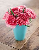 stock photo of carnations  - Pink carnations flower bouquet in a blue vase on rustic wooden background - JPG