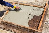 foto of slab  - Worker do cement slab cast in wooden frame in construction site - JPG