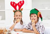 Kids with funny christmas hats munching on gingerbread cookies