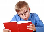 Adorable blond boy sitting at a table reading a bright red book (isolated on white background)