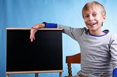 Beautiful cheerful blond boy in a grey t-shirt smiles happily presenting a small clean blackboard