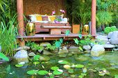 stock photo of cabana  - Sofa and table under a cabana amongst a lily pond meditation garden - JPG