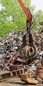 foto of scrap-iron  - inustrial machine with scrap metal grapple in front of scrap iron - JPG