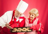 Housewife proudly shows off a fresh batch of chocolate chip cookies to a chef.