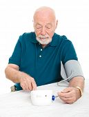 Senior man checking his blood pressure at home.  Isolated on white.