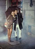 Elegant couple with umbrella on rainy evening