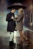 foto of overcoats  - Elegant couple with umbrella on rainy evening - JPG