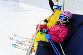 Ski lift, skiing, ski resort - happy skiers on ski lift