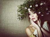 Beautiful young woman with wreath of field flowers in their hair over canvas background, toned