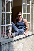 Attractive, Muscular Man Sitting On Open Window