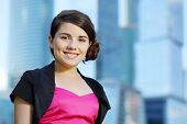 image of bolero  - Beautiful smiling girl in pink dress stands near blue skyscrapers - JPG