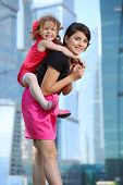 picture of bolero  - Beautiful girl carries on her back little girl in red near blue skyscrapers - JPG