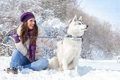 young beautiful woman sits with husky dog in the winter forest