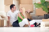 Smiling couple sitting on floor with key of new home