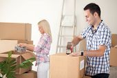 young couple packing moving boxes, ready for move out