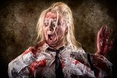 stock photo of amputation  - Halloween gore photo of a dead female zombie with bloody saw and amputated hand - JPG