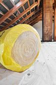 image of rafters  - A roll of insulating glass wool on an attic floor - JPG