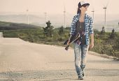 stock photo of skate board  - Beautiful Young woman walking and holding a skateboard - JPG