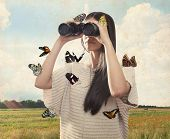 Young Woman Watching With Binocular With Butterflies