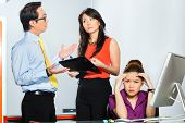 stock photo of segregation  - Asian Colleagues or coworker and manager discuss about or bullying or chicane stressed or anger employee with burn out or problems - JPG