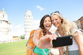 Travel tourists friends laughing taking photo with smartphone. Women girlfriends traveling in Europe