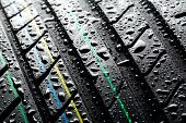 stock photo of spare  - A closeup image of a wet summer car tire with rain drops on it - JPG