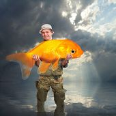 The fisherman with big Goldfish. Success concept.