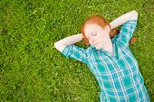 Woman Sleeping On A Green Grass Meadow