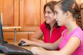 Young latin girl and her beautiful mother working on a computer and smiling