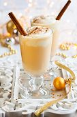 stock photo of cinnamon  - Eggnog with Cinnamon Sticks - JPG